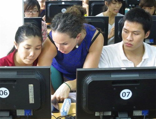 ICTP postdoc Kate Shaw (center) works with Vietnamese undergraduate physics students during a Physics without Frontiers class in 2014